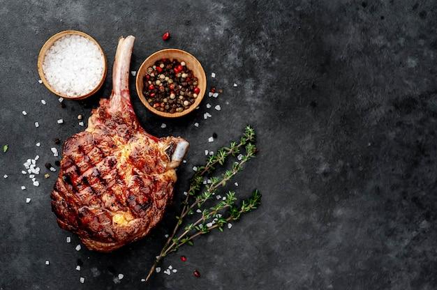 Bistecca - tomahawk di manzo alla griglia con spezie, timo su uno sfondo di pietra. con spazio copia per il tuo testo