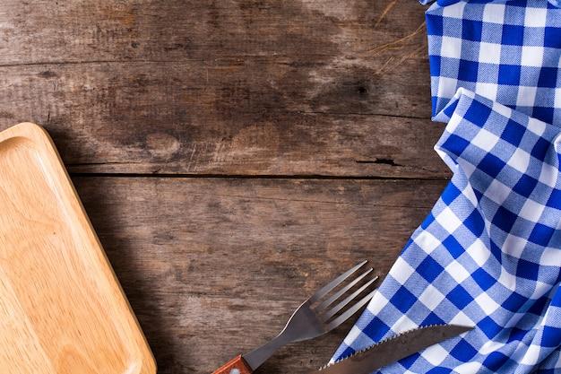 Coltello da bistecca e una forcella con tovaglia blu su fondo di legno