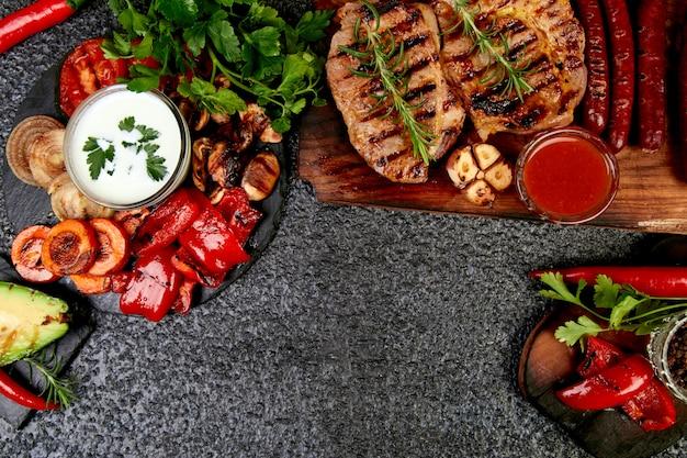 Griglia di maiale bistecca sul tagliere di legno con una varietà di verdure grigliate