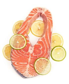 Bistecca di pesce rosso e lenon bistecca di pesce rosso e fette di limone su bianco
