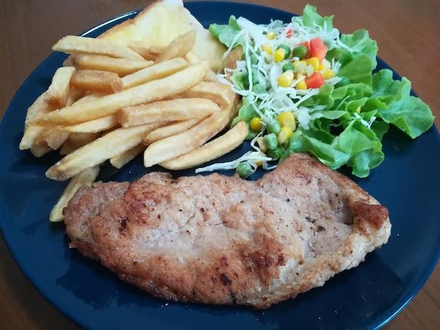 La bistecca con la salsa al pepe nero e l'insalata di patate e pomodori su legno