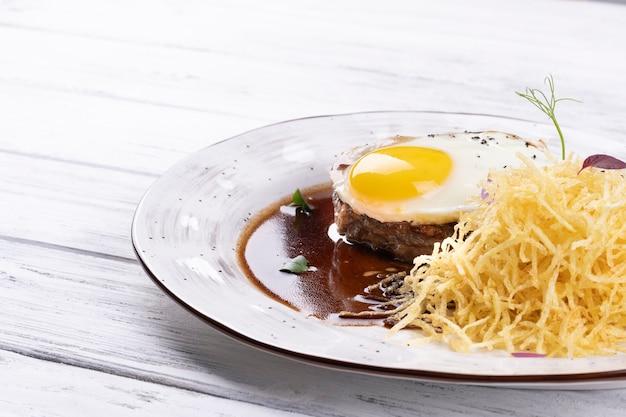 Bistecca con uovo su un piatto bianco e un fondo di legno bianco
