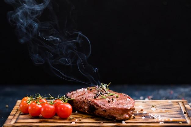 Menù della bistecca. costata di manzo. primo piano di carne di manzo alla griglia con pomodorini e rametto di rosmarino in fiamme.