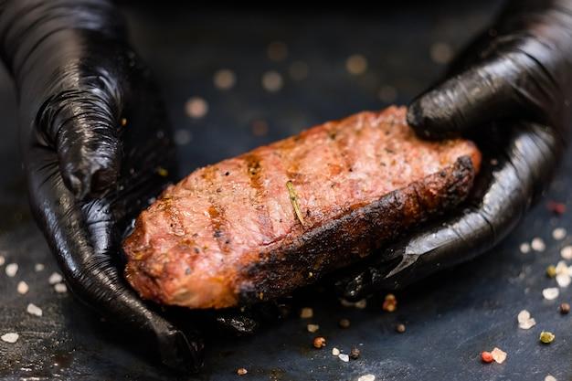 Menù della bistecca. bistecca di filetto. primo piano delle mani dello chef che tengono carne di manzo alla griglia.