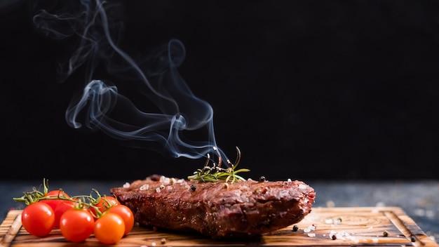 Menù della bistecca. bistecca di filetto. carne di manzo alla griglia con pomodorini e rametto di rosmarino bruciato.