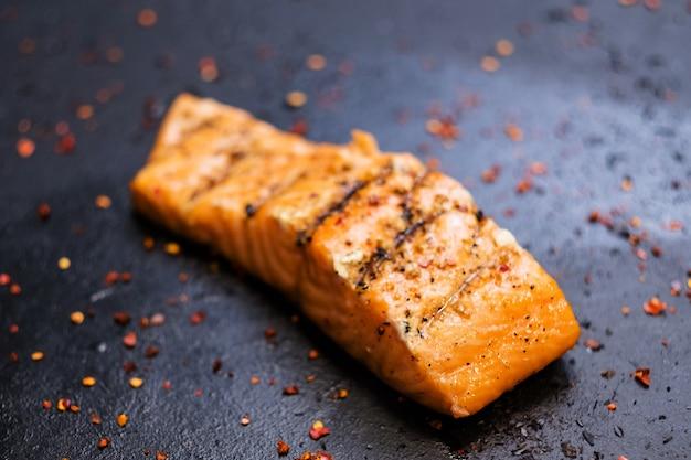 Steakhouse e ristorante di pesce. primo piano del pezzo succoso di filetto di salmone affumicato con condimento colorato.