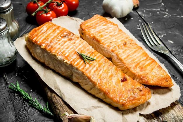 Bistecche di salmone alla griglia con spezie e pomodori sul tavolo rustico scuro.