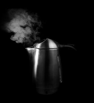 Vapore su sfondo nero e acqua bollente in un bollitore d'argento