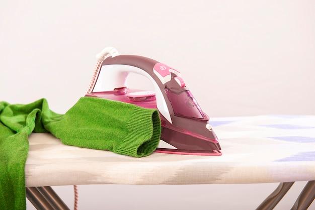 Ferro da stiro a vapore e vestiti da stiro maglione verde sull'asse da stiro isolato.