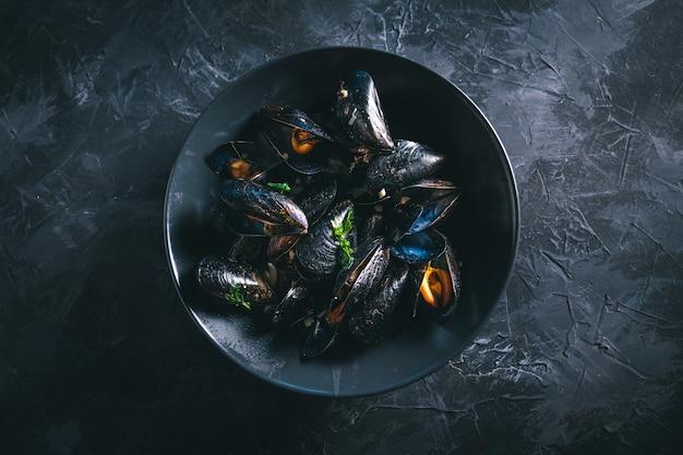 Cozze al vapore in una ciotola nera su un tavolo scuro