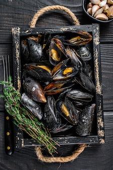 Cozze al vapore con gusci in un vassoio di legno con erbe aromatiche