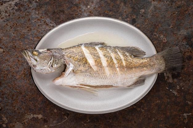 Pesce al vapore della spigola in piatto ceramico ovale su fondo arrugginito di struttura, vista superiore, spigola, pesce persico gigante, barramundi, barra