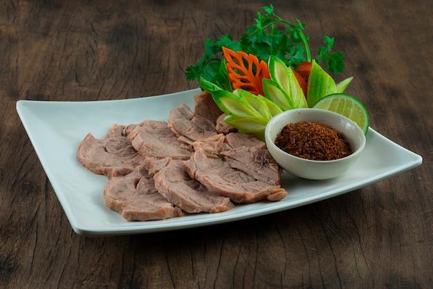 Stinco di manzo al vapore servito in pasta di peperoncino galangal (nam-prik-kha) cibo tailandese vista laterale in stile lanna settentrionale