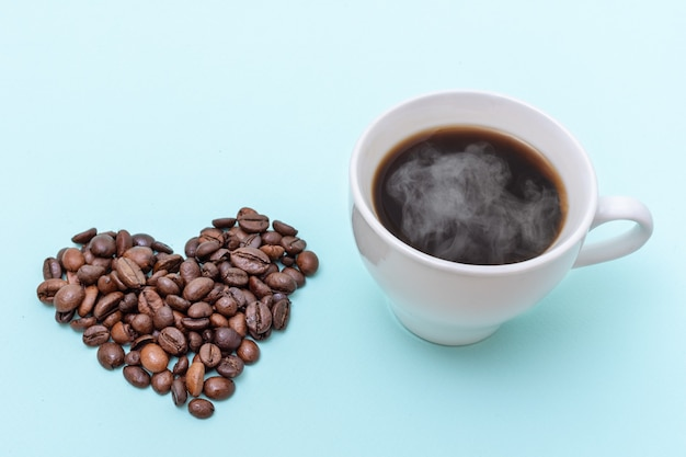 Tazza di caffè fumante, chicchi di caffè a forma di cuore su sfondo blu, copia dello spazio.
