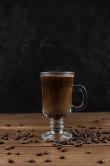 Caffè fumante su superficie in legno e sfondo nero.