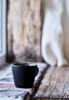 Tazza fumante con caffè ristretto su mattoni e legno d'epoca