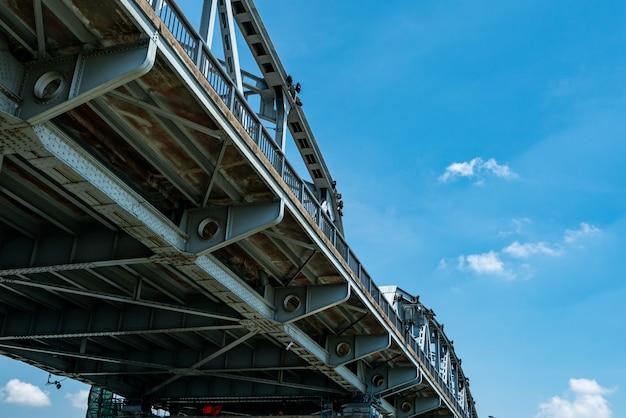 Struttura d'acciaio del ponte contro cielo blu e le nuvole bianche. costruzione di ingegneria del ponte di ferro. ponte metallico forte e resistente.