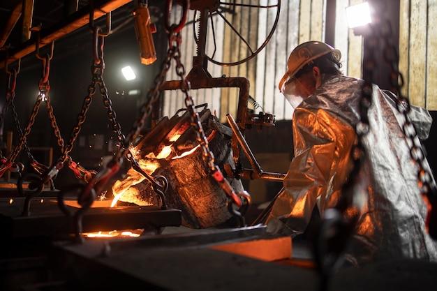 Processo di fusione dell'acciaio e operaio in fonderia riempiendo stampi con ferro fuso.