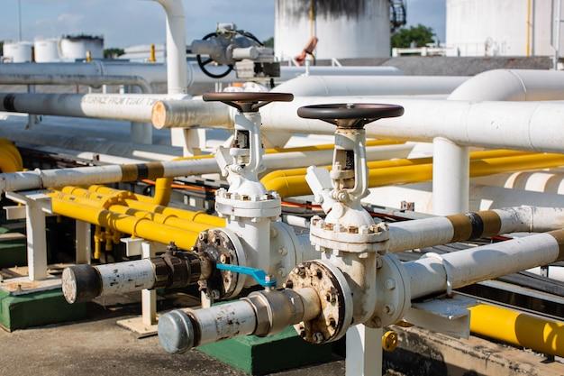 Tubi lunghi in acciaio e gomito del tubo della valvola nella fabbrica di petrolio della stazione durante la raffineria.
