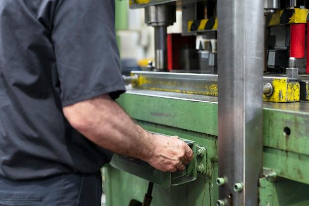 Impianto di produzione di acciaio un lavoratore sta posizionando un pezzo di metallo all'interno della pressa la pressa viene spinta verso il basso il processo di produzione della metallurgia da vicino