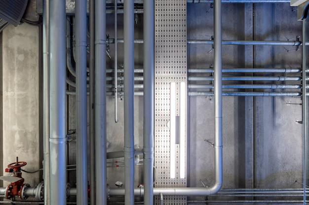 Rete di sistemi di tubi in acciaio sul soffitto di malta nell'edificio