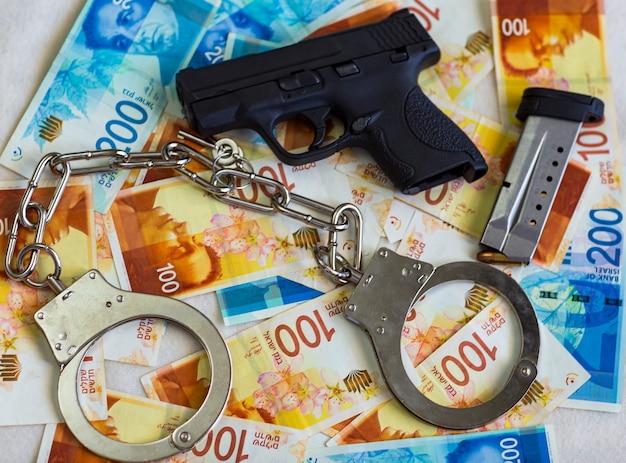 Manette d'acciaio della polizia, pistola da 9 mm, proiettili sullo sfondo di banconote del nuovo shekel israeliano con banconote da 100, 200 nis. manette e banconote, contanti. frode aziendale, reato fiscale e corruzione