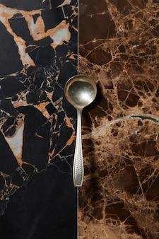 Cucchiaio d'acciaio su uno sfondo di marmo marrone scuro
