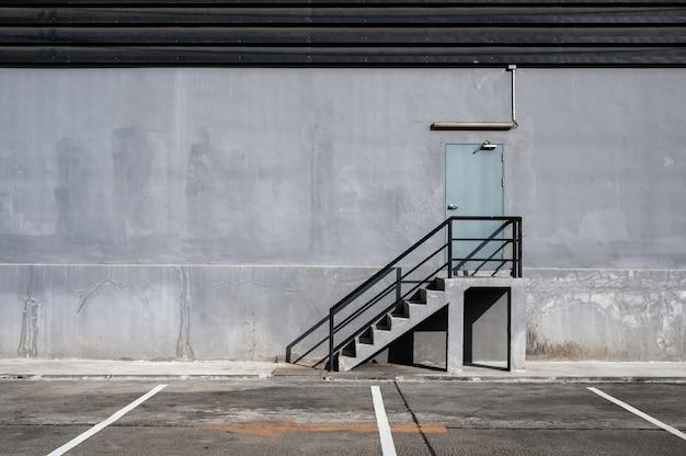 Scala in acciaio e porta tagliafuoco e parcheggio presso il magazzino di distribuzione