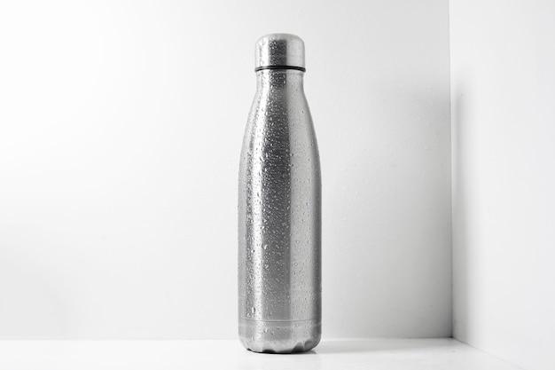 Bottiglia termica in acciaio spruzzata con acqua su bianco.