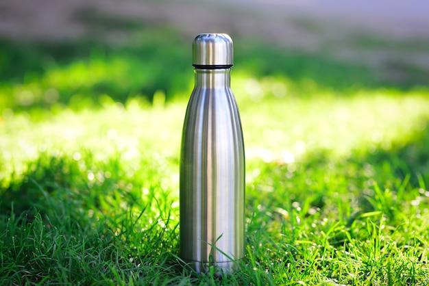 Bottiglia d'acqua termica in acciaio d'argento su sfondo di erba sfocata con spazio di copia