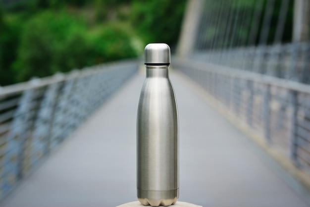 Bottiglia d'acqua in acciaio sullo sfondo della pista ciclabile in mezzo alle montagne copia spazio