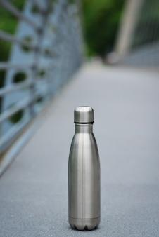 Bottiglia d'acqua in acciaio sullo sfondo della pista ciclabile in mezzo alle montagne