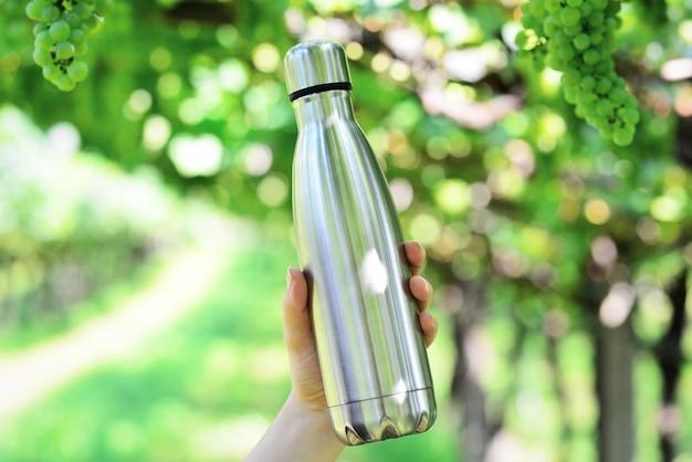 Bottiglia d'acqua in acciaio su sfondo di vigneto