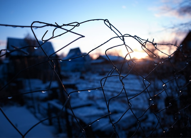 Recinzione in filo d'acciaio durante il tramonto sullo sfondo