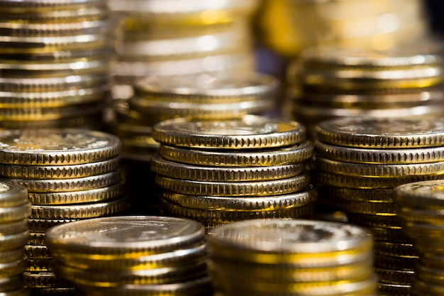 Acciaio con una mescolanza di altri metalli, monete lavorate per dare loro una tonalità dorata, le monete sono vere e usate come mezzo di pagamento, le monete sono vecchie e presentano alcuni difetti, primo piano