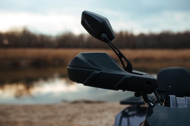 Il volante di un atv sullo sfondo un fiume e sabbia. sport e concetto estremo