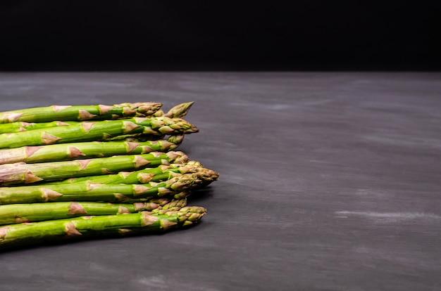 Gambi di asparagi verdi freschi su sfondo nero. raccolto stagionale primaverile. lay piatto, copia spazio. concetto di cibo sano. avvicinamento