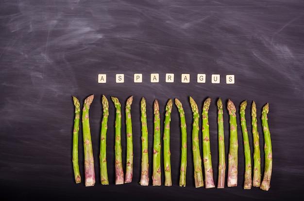 Gambi di asparagi verdi freschi su una lavagna nera. raccolto stagionale primaverile. lay piatto, copia spazio. concetto di cibo sano. vista dall'alto.