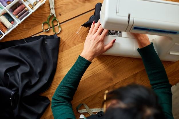 Passo dopo passo, una donna di 50 anni cuce vestiti sulla macchina da cucire, sarto maturo che lavora con il cucito in atelier, industria tessile, hobby, spazio di lavoro. processo di creazione fai da te, posto di lavoro di sarta.