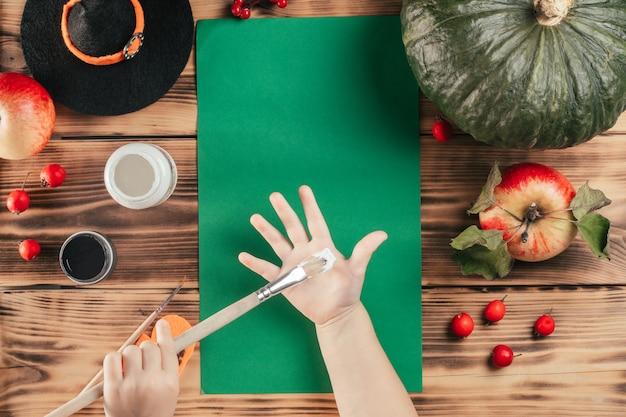 Tutorial passo-passo di halloween con l'impronta della mano del bambino dei fantasmi. fase 2: il bambino applica la vernice bianca sul palmo della mano con il pennello. vista dall'alto
