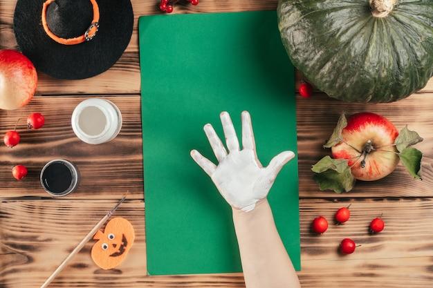 Tutorial passo-passo di halloween con l'impronta della mano del bambino dei fantasmi. passaggio 3: palmo del bambino, completamente imbrattato di vernice. vista dall'alto