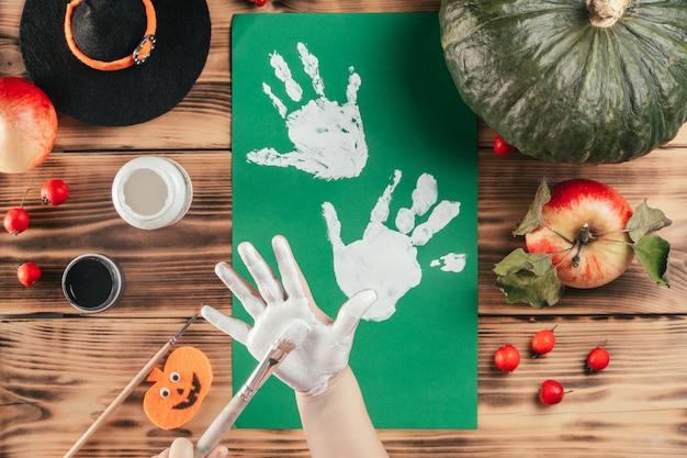 Tutorial passo-passo di halloween con l'impronta della mano del bambino dei fantasmi. passaggio 5: il bambino applica la vernice bianca sul palmo della mano con il pennello. vista dall'alto