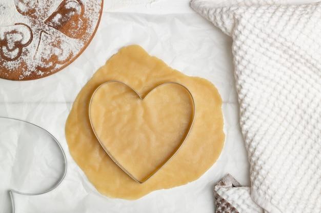 Istruzioni dettagliate per la ricetta della torta a forma di cuore. passaggio 5. stendete ogni pezzo di pasta e tagliatelo a forma di cuore. lay piatto.