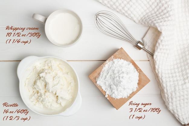 Istruzioni dettagliate per la ricetta della torta a forma di cuore. passaggio 6, ingredienti per la crema. zucchero a velo, ricotta, panna da montare. lay piatto.
