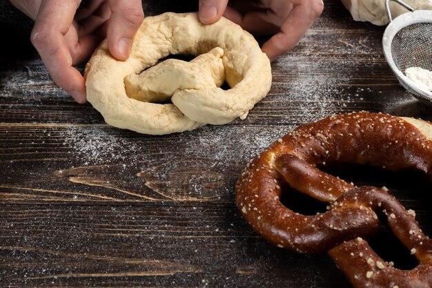 Istruzioni dettagliate per preparare i pretzel. il cuoco stende la pasta e stende il pretzel
