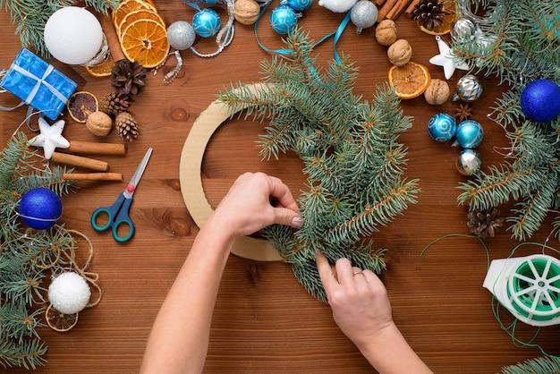 Processo graduale per creare una ghirlanda di alberi di natale a casa con rami di abete rosso, arance e palle di natale