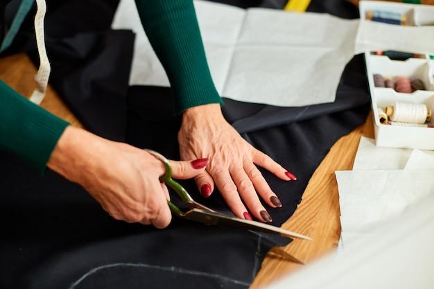 Passo dopo passo, la sarta da donna passa il materiale da taglio con le forbici sul tavolo, sarto maturo che lavora in atelier, industria tessile, hobby, spazio di lavoro. processo di creazione fai da te, posto di lavoro di sarta.