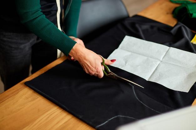 Passo dopo passo, sarta donna mani taglio di materiale con le forbici sul tavolo, sarto maturo che lavora in atelier, industria tessile, hobby, area di lavoro.