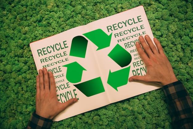 Passo alla vita verde. immagine ravvicinata vista dall'alto dell'uomo che si tiene per mano sul suo taccuino con simbolo di riciclo e testo su sfondo muschio