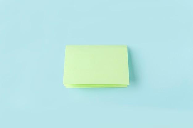 Fase tre di come realizzare una farfalla di carta origami con carta verde, forbici su sfondo blu